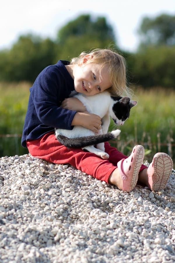 Kind, das eine Katze umarmt. lizenzfreie stockfotografie