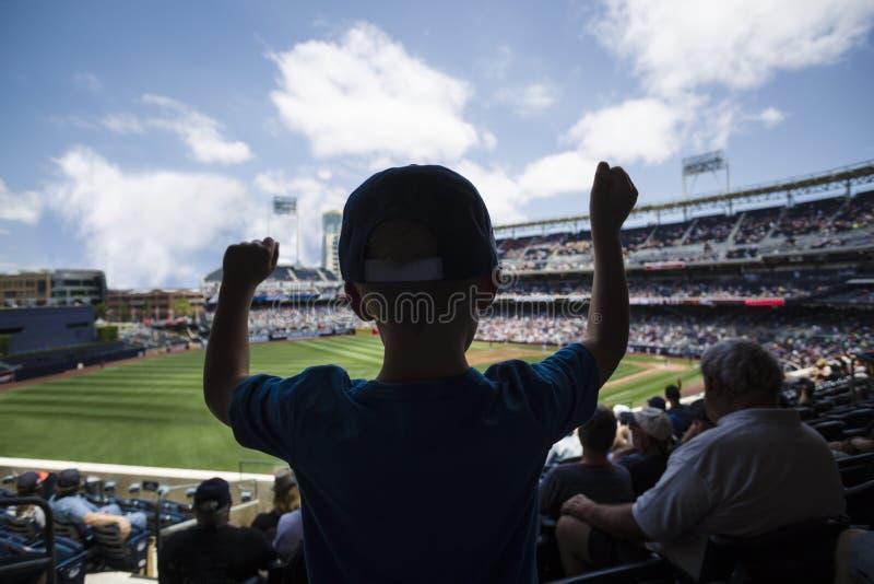 Kind, das an einem Baseballspiel steht und zujubelt lizenzfreie stockbilder