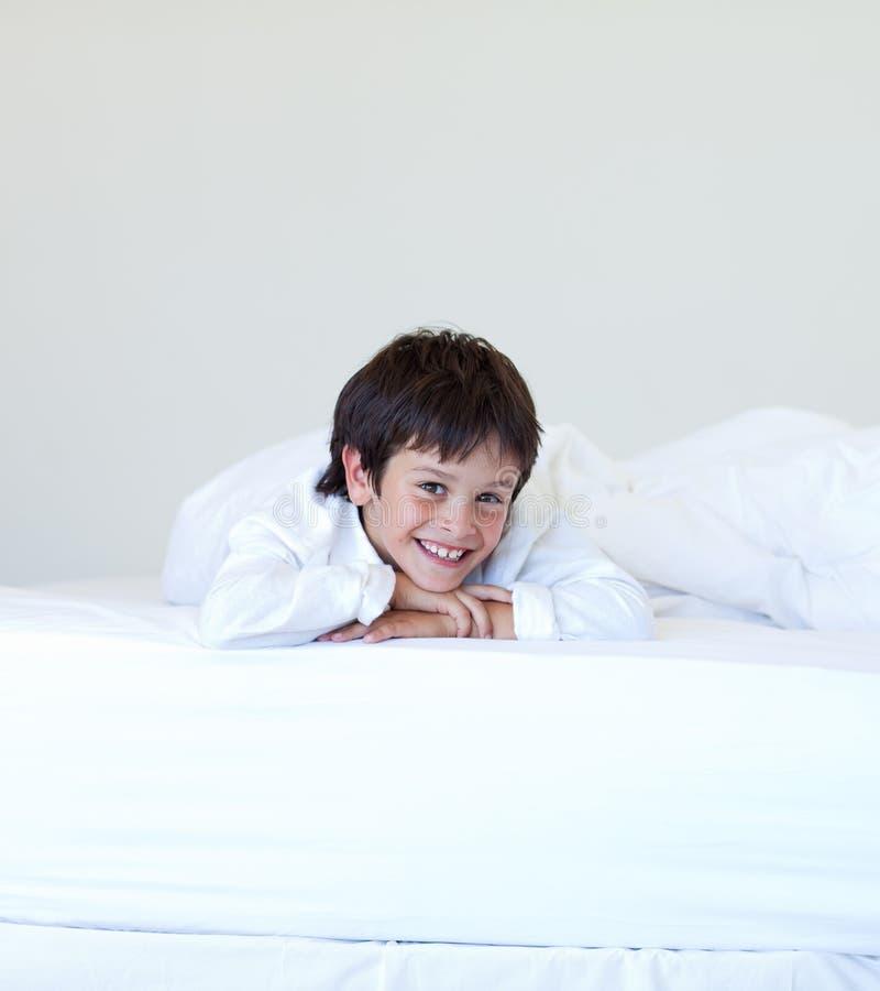 Kind, das in einem Bett lächelt lizenzfreie stockfotografie