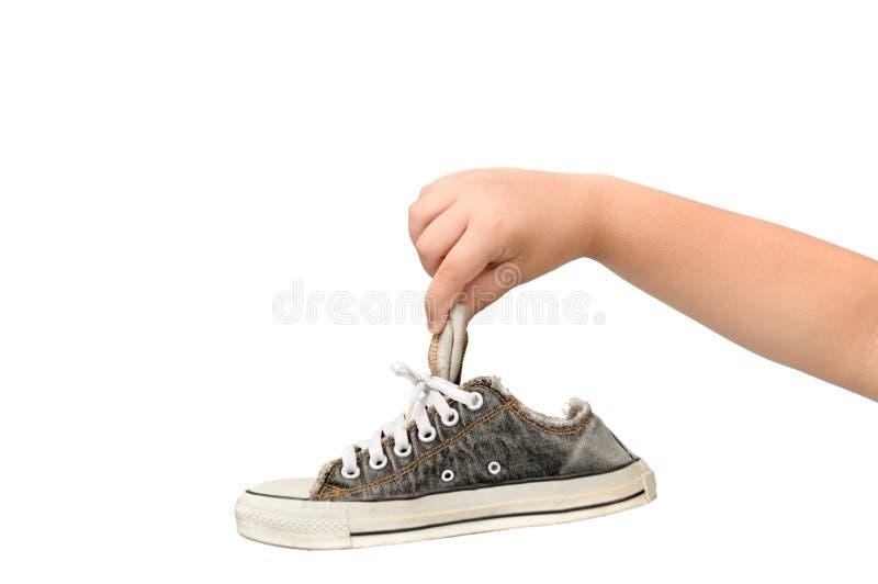 Kind, das einen alten schmutzigen und stinkenden Turnschuh hält lizenzfreies stockfoto