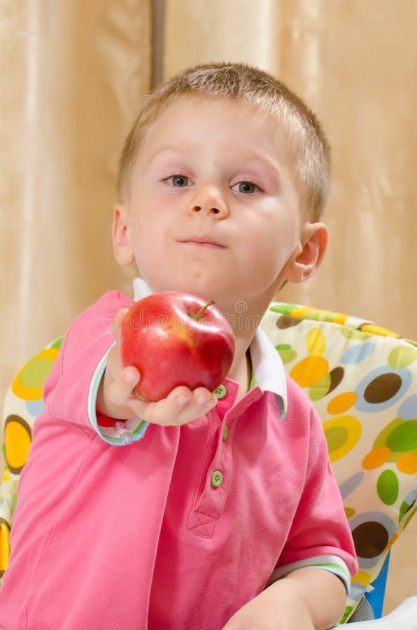 Kind, das einen Apfel anbietet stockbilder
