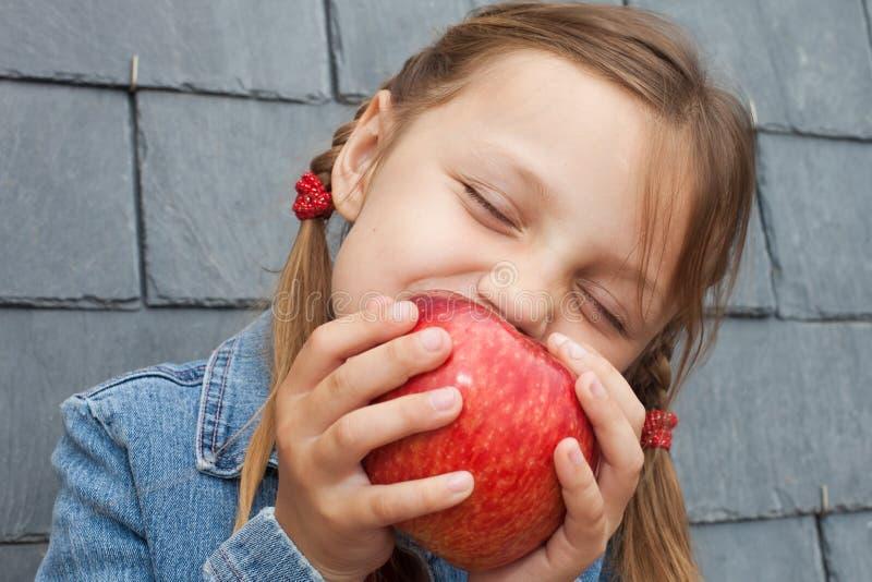 Kind, das einen Apfel isst stockfotos