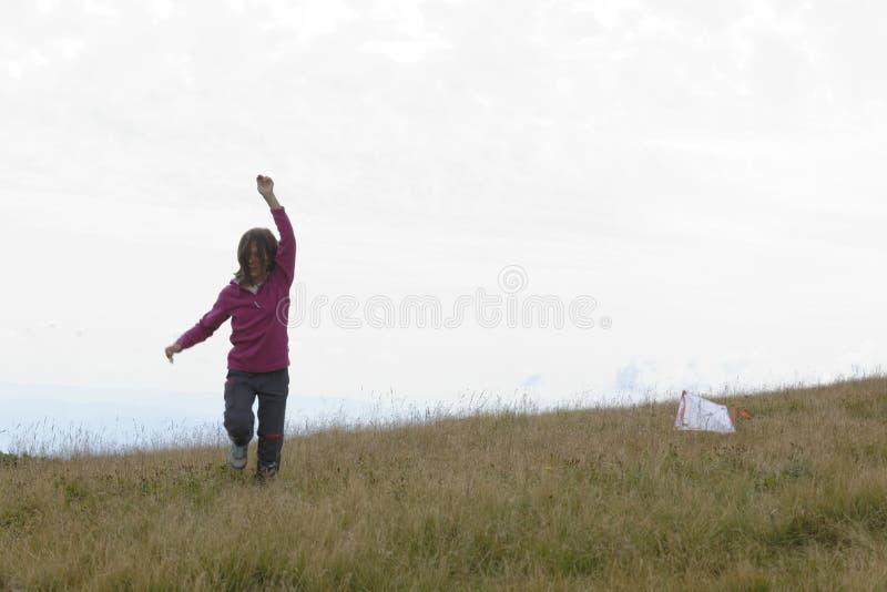 Kind, das einen Drachen fliegt stockbild