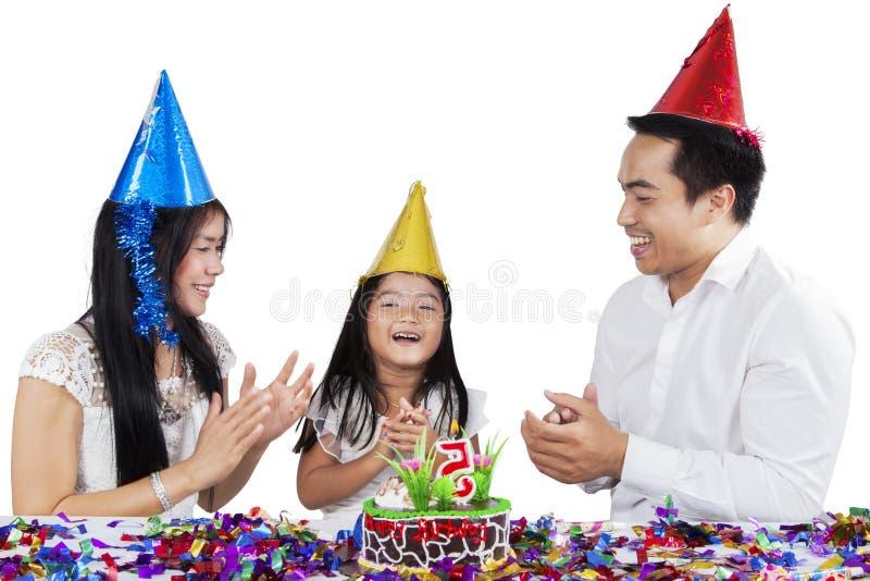 Kind, das einen Geburtstag mit ihren Eltern feiert stockfotografie