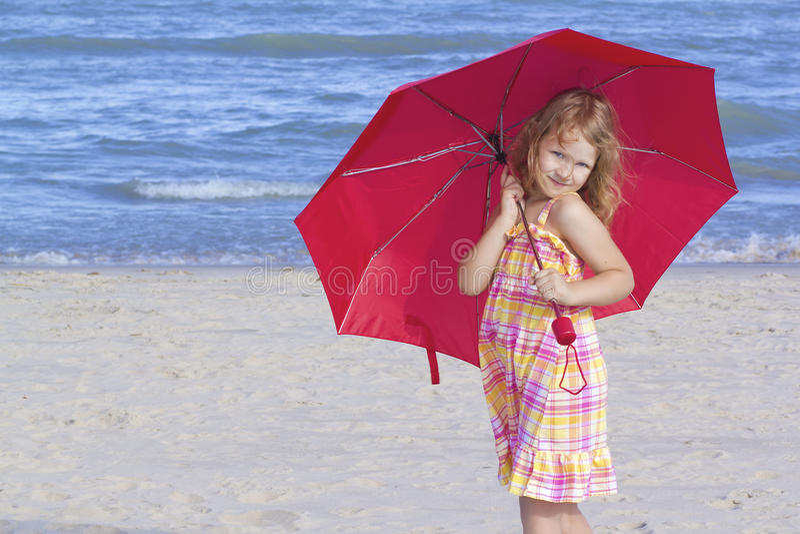 Kind, das einen roten Regenschirm am Strand anhält stockfotografie