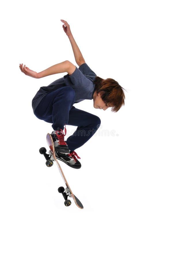 Kind, das einen Trick auf Skateboard übt stockfotografie