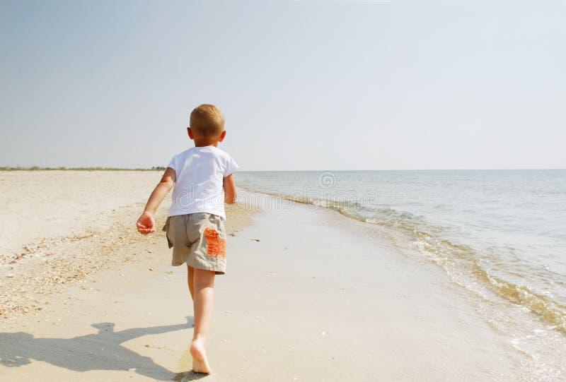 Kind, das entlang Strand läuft lizenzfreie stockfotos