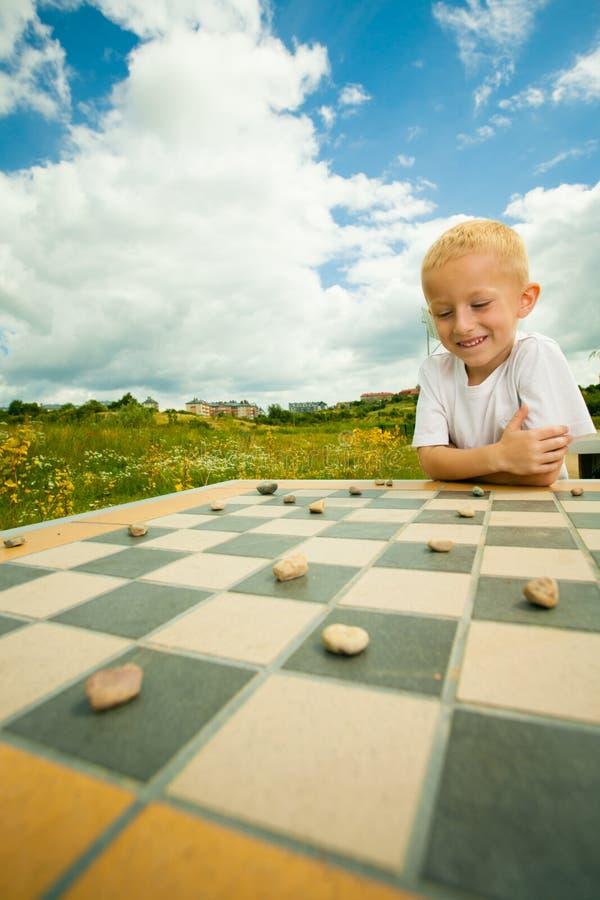 Kind, das Entwürfe oder das KontrolleurBrettspiel im Freien spielt stockbild