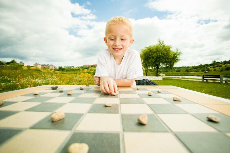 Kind, das Entwürfe oder das KontrolleurBrettspiel im Freien spielt lizenzfreies stockbild
