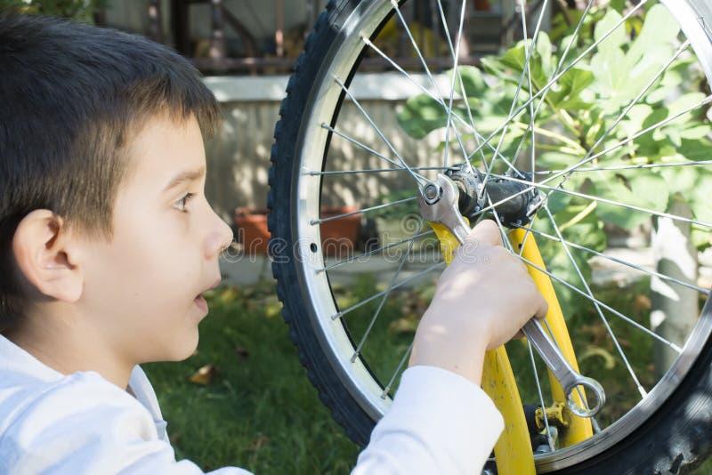 Kind, das Fahrräder reparieren stockfotografie