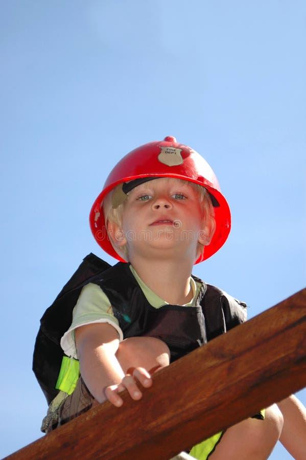 Kind, das Feuerwehrmann spielt stockfotografie