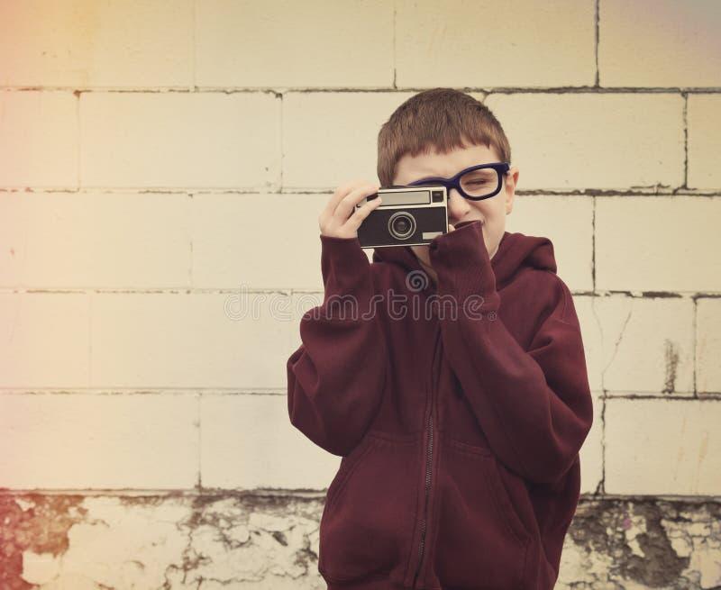 Kind, das Foto mit Weinlese-Kamera macht stockfotos