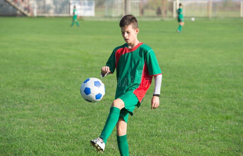 Kind, das Fußball spielt lizenzfreies stockbild