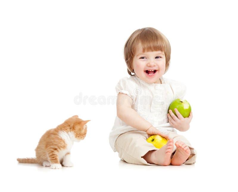 Kind, das gesunde Nahrung der Äpfel mit Katze isst stockbild