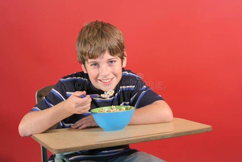 Kind, das Getreide am Schreibtisch isst lizenzfreie stockbilder