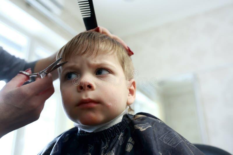 Kind, das Haarschnitt hat stockfotografie