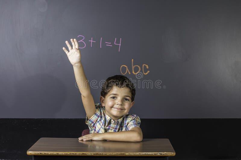 Kind, das Hand im Klassenzimmer anhebt. lizenzfreie stockfotos