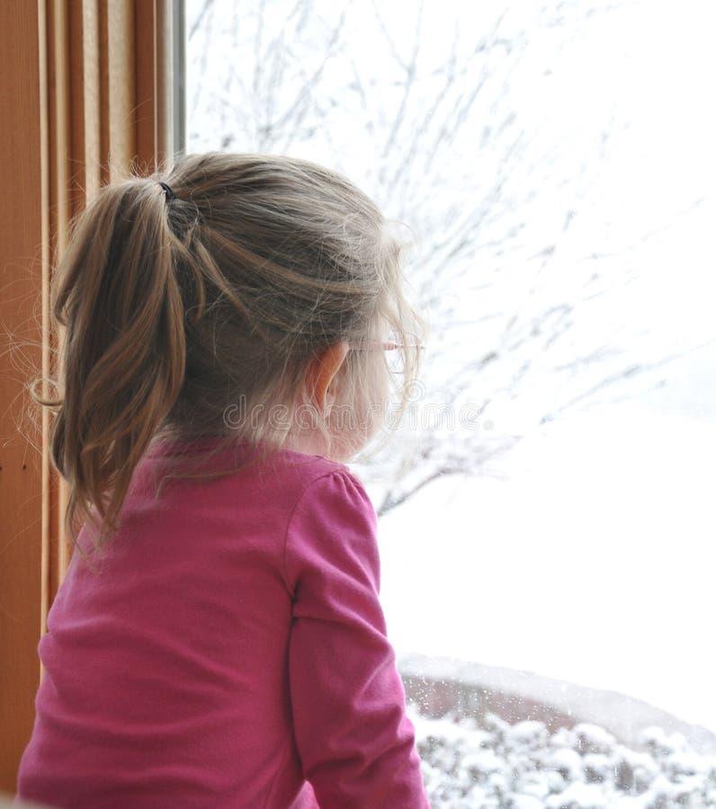 Kind, das heraus Winter-Fenster schaut stockfotos