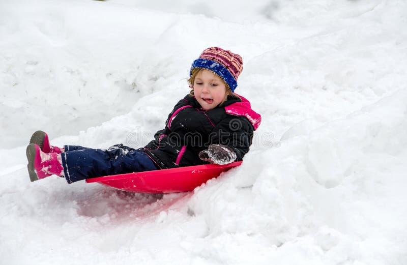 Kind, das hinunter einen gefrorenen Hügel schiebt lizenzfreie stockfotos