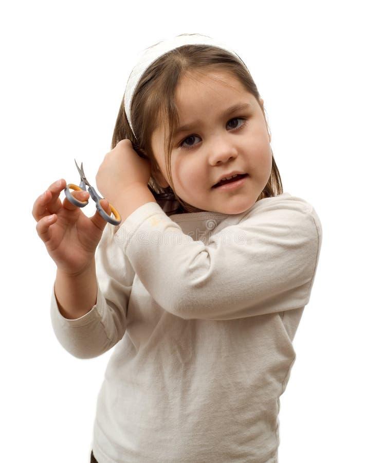 Kind, das ihr eigenes Haar schneidet lizenzfreie stockfotografie