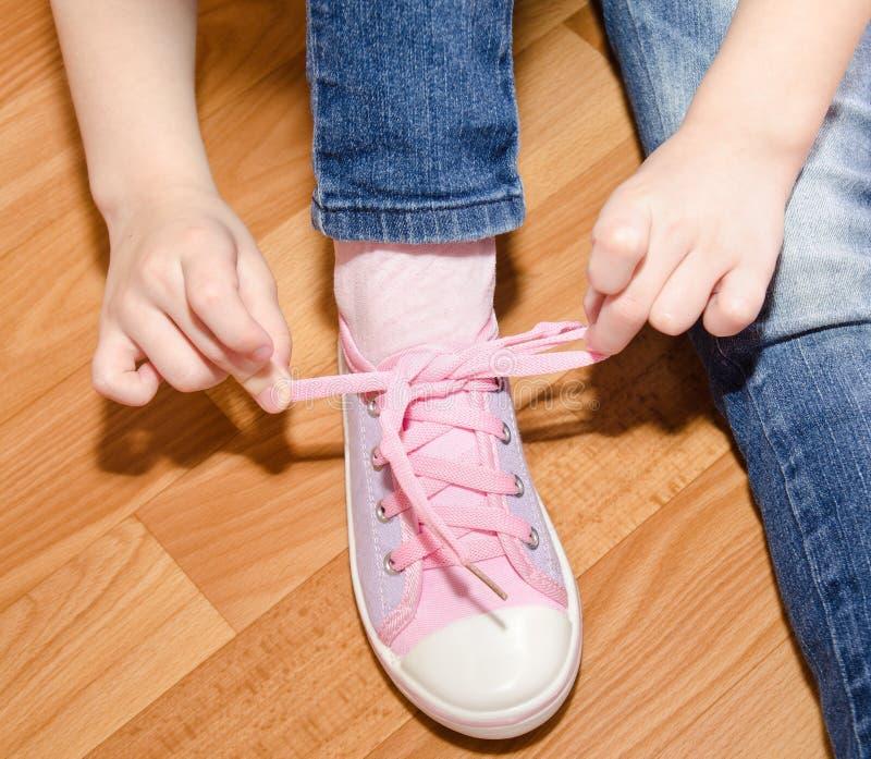 Kind, das ihre Schuhe sitzen auf dem Boden bindet stockfotografie