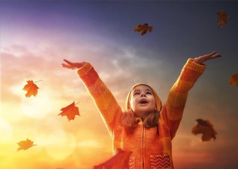 Kind, das im Herbst spielt stockfotografie