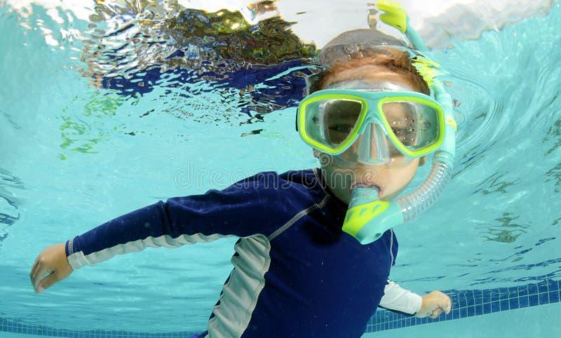 Kind, das im Pool schnorchelt und schwimmt lizenzfreie stockfotografie