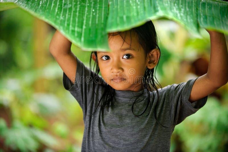Kind, das im Regen spielt stockfotos