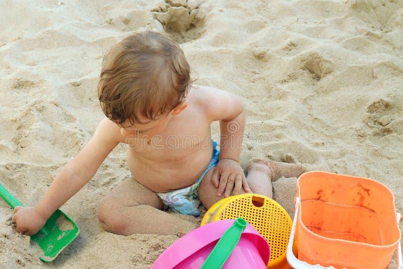 Kind, das im Sand spielt stockfotos