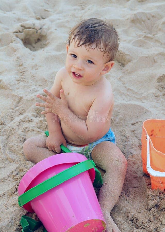 Kind, das im Sand spielt stockbild