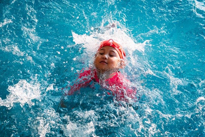 Kind, das im Spritzwasser spielt stockfotos
