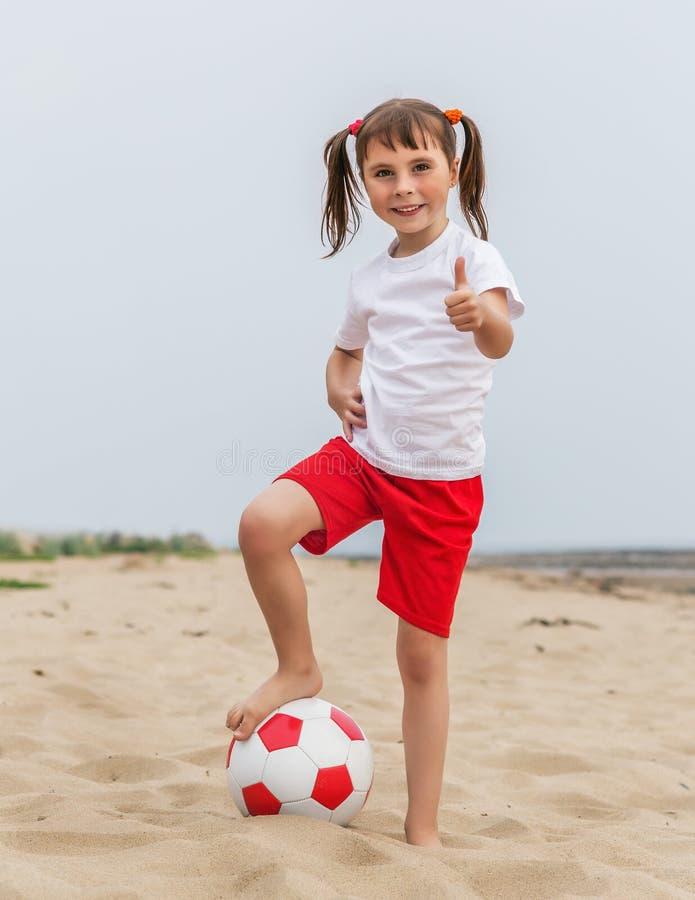 Kind, das im Strandfußball spielt stockfotografie