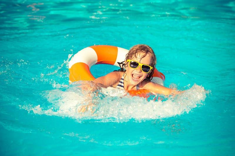 Kind, das im Swimmingpool spielt lizenzfreie stockfotografie