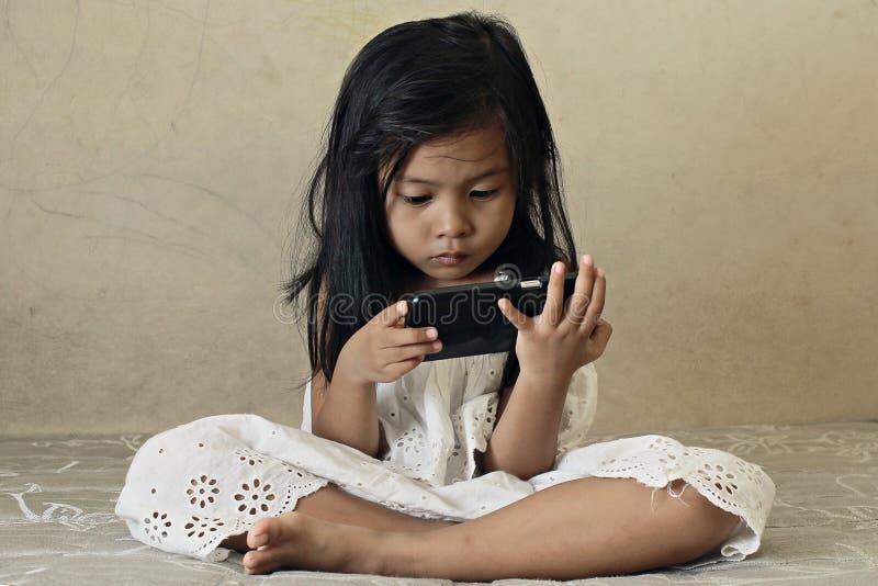 Kind, das intelligentes Telefon aufpasst stockfoto