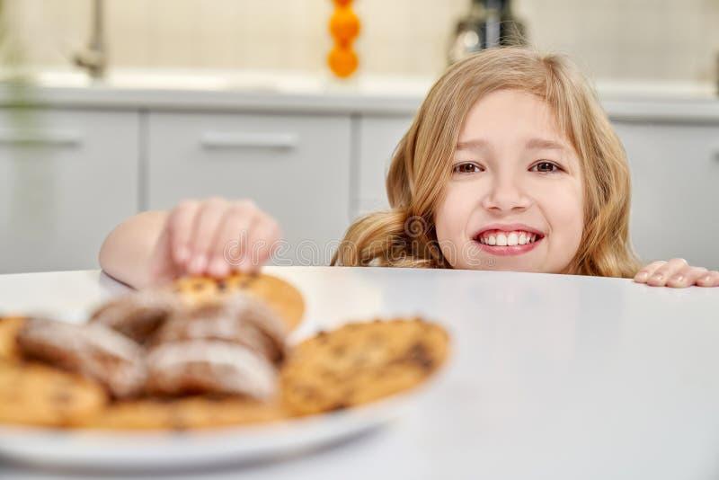 Kind, das Kekse mit Rosinen von der Tabelle versteckt und nimmt stockbilder