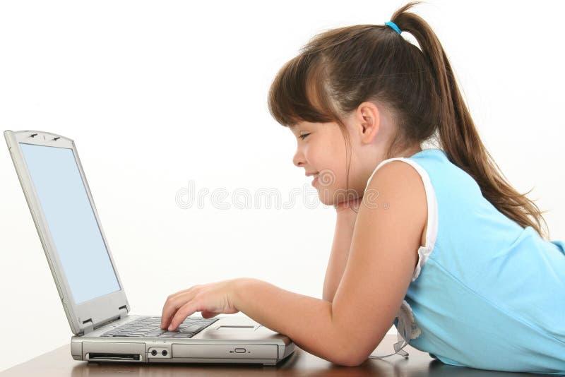 Kind, das an Laptop arbeitet lizenzfreie stockfotografie