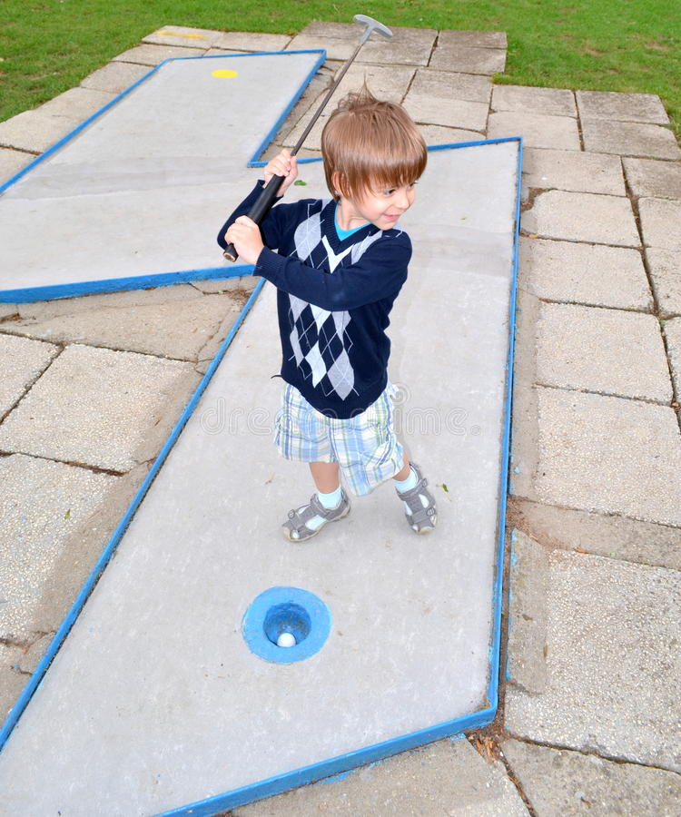 Kind, das Minigolf spielt stockbild