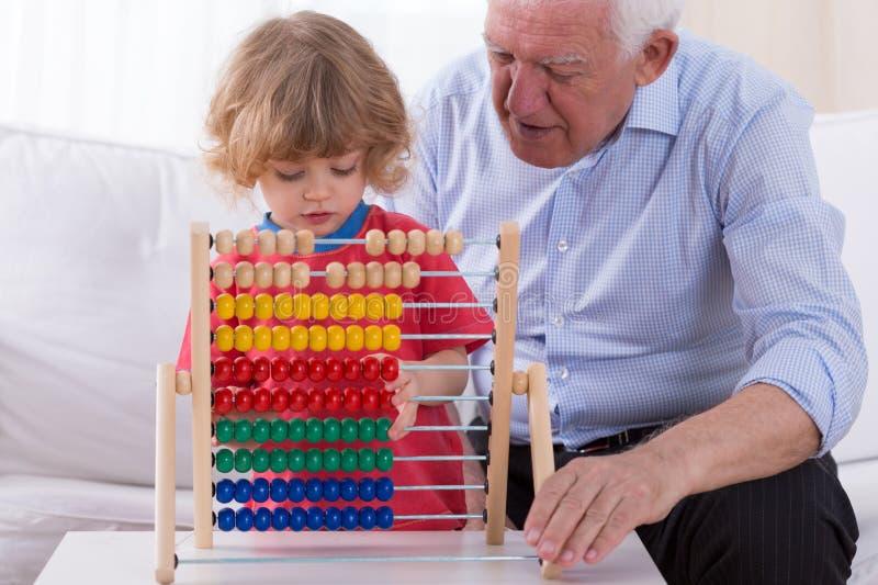 Kind, das mit Abakusspielzeug spielt stockbild