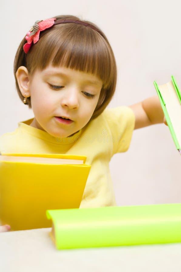 Kind, das mit Büchern spielt stockfotos