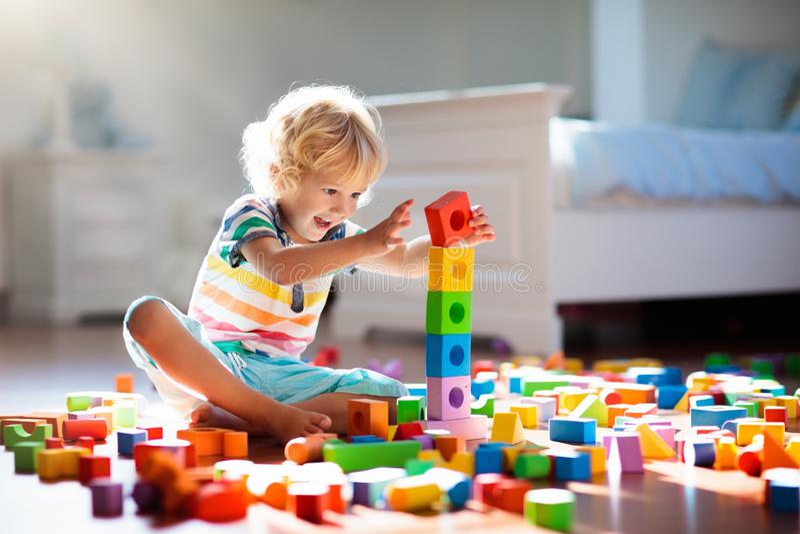 Kind, das mit bunten Bauklötzen spielt Kinderspiel lizenzfreies stockbild
