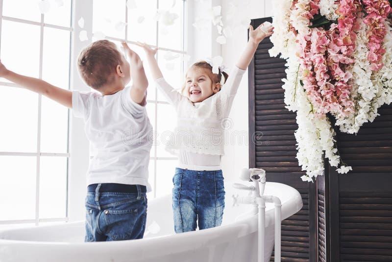 Kind, das mit den rosafarbenen Blumenblättern im Hauptbadezimmer spielt Wenig Mädchen und fawing Spaß und Freude des Jungen zusam stockbilder