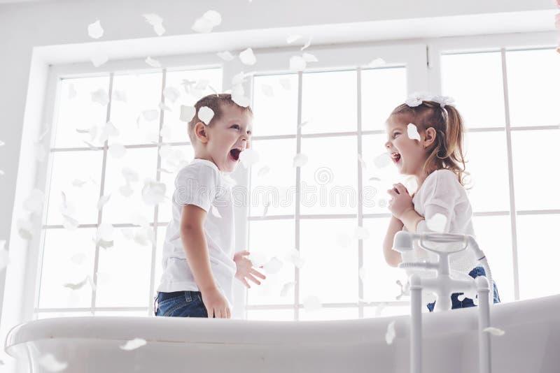 Kind, das mit den rosafarbenen Blumenblättern im Hauptbadezimmer spielt Wenig Mädchen und fawing Spaß und Freude des Jungen zusam stockfotografie