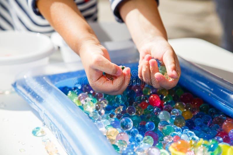 Kind, das mit der farbigen Glaskugel, Spiel mit farbigen Bällen spielend spielt lizenzfreies stockbild