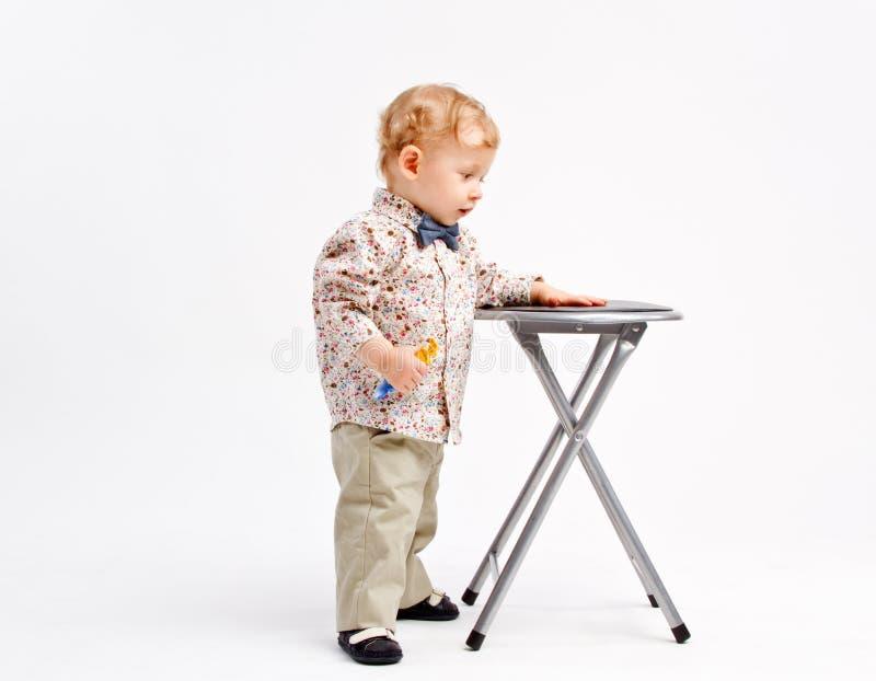 Kind, das mit einem Schemel vergleicht lizenzfreie stockfotografie