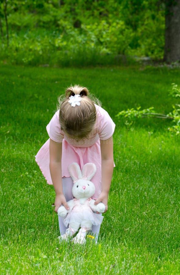 Kind, das mit einem Spielzeughäschen im Garten spielt lizenzfreies stockbild