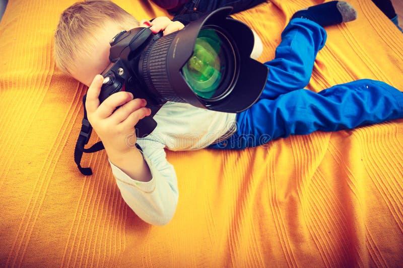 Kind, das mit großer Berufsdigitalkamera spielt lizenzfreie stockbilder