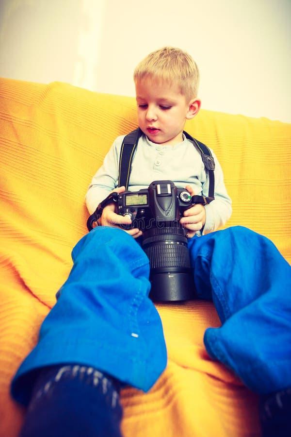 Kind, das mit großer Berufsdigitalkamera spielt lizenzfreies stockbild