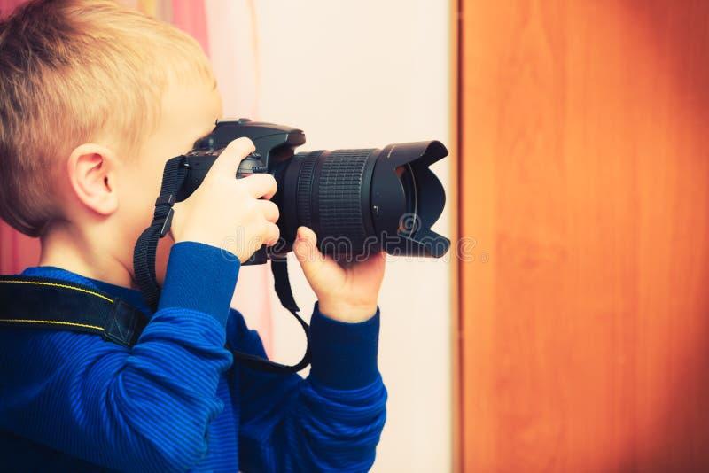Kind, das mit großer Berufsdigitalkamera spielt stockbild