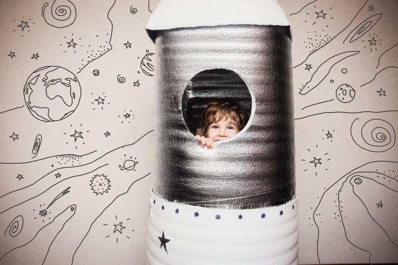 Kind, das mit großer handgemachter Rakete spielt stockbilder