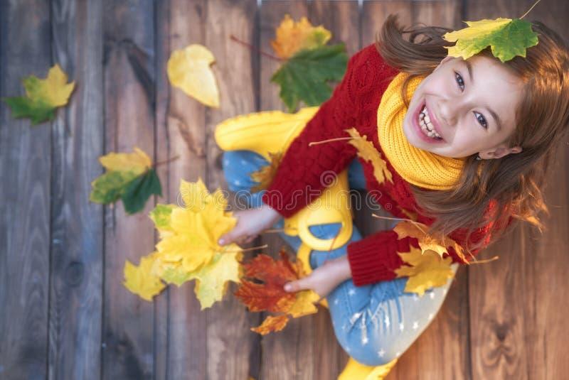Kind, das mit Herbstlaub spielt lizenzfreies stockfoto